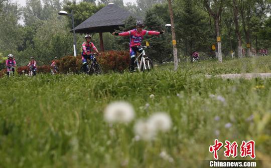"""第5届北京国际自行车骑游大会将于6月27日至28日举行,5000余名世界各地的车手将""""骑""""聚延庆。28日,报名工作正式启动。图为延庆骑行者。 张浩 摄"""