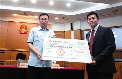 昨天,一中院履行局局长吴小成(左)将20亿元的支票,交到了华懋公司代表庄日杰的手中。新京报记者 王贵彬 摄