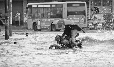 6月3日,一辆摩托车在贵州安顺城区冒大雨出行。当日,我国南方强降雨天气持续,贵州、江西等地受灾严重。