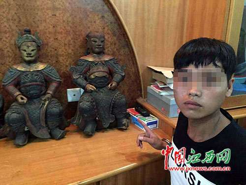怀疑人指认被盗的木雕菩萨。