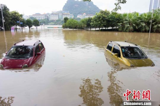 6月15上午9点,柳江河郊区水位迫近戒备水位,滨江路上很多商店商店、汽车被水吞没。 黄威铭 摄
