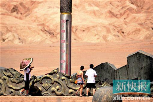 14日下午,游客在火焰山风景区巨型电子温度计前游览。