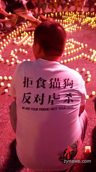 """自愿者身穿""""拒食猫狗,否决虐杀""""的文明衫。"""