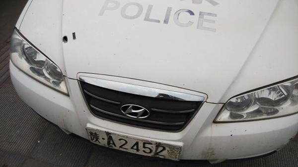 现场有警车疑似被子弹击中。