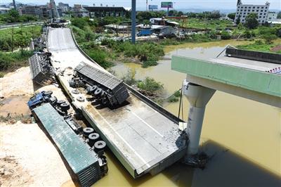 昨日,出事的匝道和4辆满载瓷土的重载五型货车掉落地上。 新华社记者 卢汉欣 摄