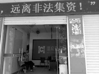 """涉嫌非法集资被警方立案的河南浩宸投资担保有限公司西平分公司,门口的LED广告牌上显示""""远离非法集资""""的字样。"""