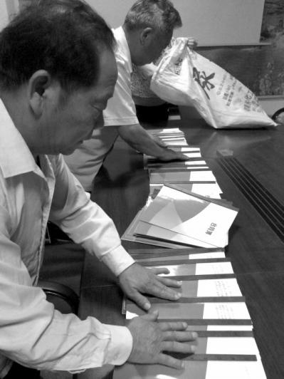 武金成向记者展示业务员与公司签订的合同。