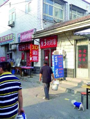 """彩票店藏身在水屯集贸市场,门口挂着写有""""3D彩票""""二字的灯箱。"""