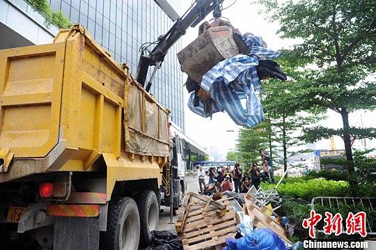 """6月24日,香港特区当局地政总署法律人员清算不法""""占中""""以后留传在立法会和当局总部外的帐子和其余物件。中新社发 谭达明 摄"""
