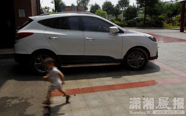 6月28日,湘潭华俏丽都社区,失事的车子还停在社区里,一小伴侣从车子边跑过。图/潇湘晨报记者华剑