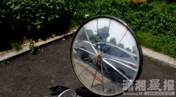 6月28日,湘潭某社区,失事的车子映在一块破裂的摩托车后镜里。图/潇湘晨报记者华剑