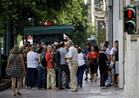 希腊民众在街头ATM机前排长队取现金。