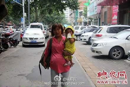 抱着孩子乞讨的孕妇。