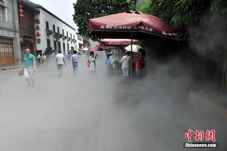 7月1日消息。近日,福州持续高温天气,三坊七巷启动了喷水雾装置,每5分钟喷雾一次,为景区降温,为游客送清凉。图为民众在三坊七巷游玩。 吕明 摄