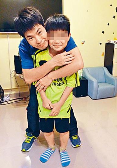 香港单亲爸爸郑欢恒在访问时合照,紧紧地揽抱儿子。图自香港《星岛日报》