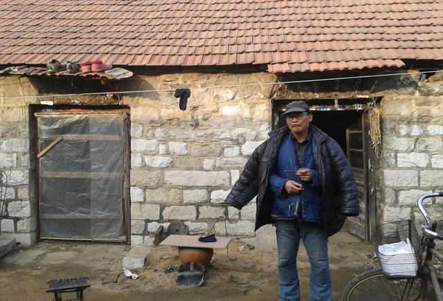 一位老农民和他背后破旧的房子