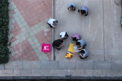 亲人们在刘亚磊坠楼处祭奠。新京报记者 周岗峰 摄