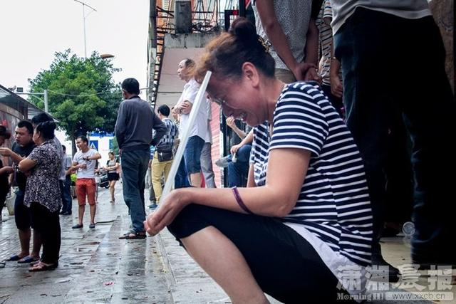 7月4日,望城区金源旅馆门口,李娟(化名)的姑姑正拿着她的照片低头痛哭。图/潇湘晨报记者 谢长贵 实习生 陈日雯