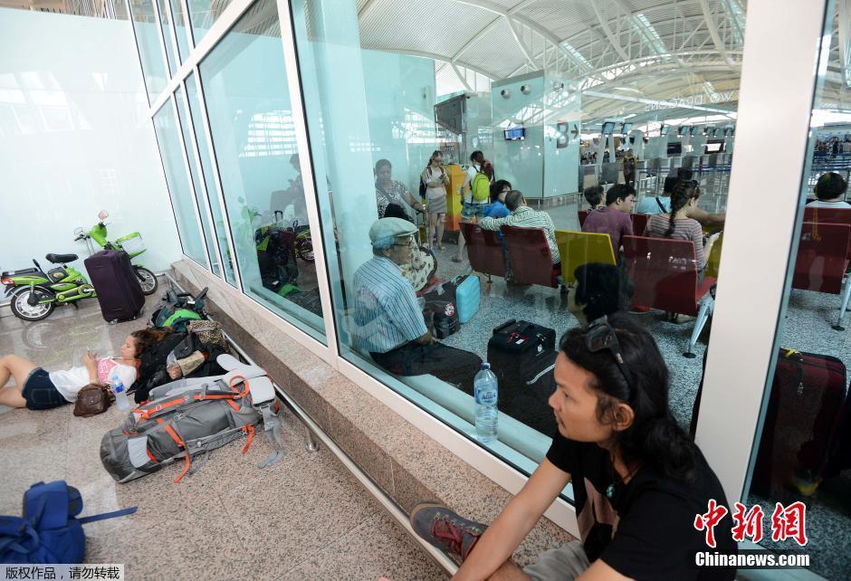 当地时间2015年7月10日,印尼登巴萨,外籍游客在国际机场等待航班信息。由于印尼东爪哇的拉翁火山已经喷发了一周,由于喷出的烟灰仍可能影响航空安全,印尼当局取消了277个航班,其中包括117个国际航班。