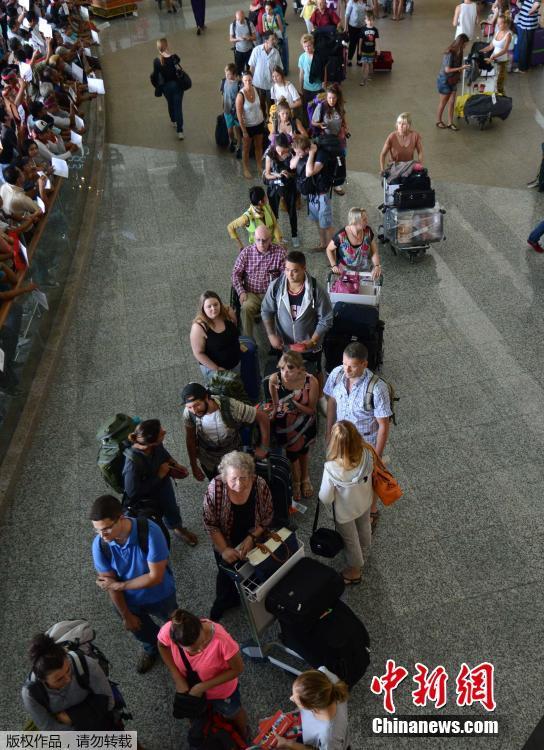 当地时间2015年7月14日,印尼巴厘岛登巴萨,乘客在机场排长队。印尼东爪哇省拉翁火山日前喷发导致火山灰弥漫,导致巴厘岛国际机场暂时关闭,约900架航班取消或延误,在假日旺季给游客带来巨大困扰。