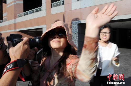 图一:外逃贪官乔建军前妻赵世兰5月在洛杉矶出庭,离开法庭时躲避并阻止记者采访拍摄。 中新社发 毛建军 摄