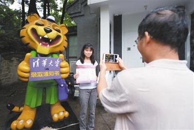 昨日下午,人大附中毕业生王浩昀成为今年首个拿到清华大学录取通知书的北京考生,父亲在清华大学招办门前,为其拍照留念。 新京报记者 许路阳 摄