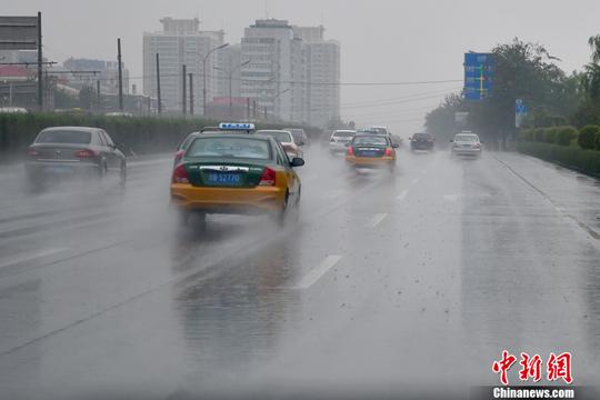 图为租借车在积水的路途下行驶,溅起水花。中新网记者 金硕 摄