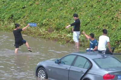 男子在积水中摸到本人的车牌。京华时报记者 赵思衡 摄