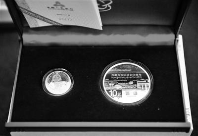 图为西藏自治区成立50周年金银纪念币(7月18日摄)。 当日,由中国人民银行发行的西藏自治区成立50周年金银纪念币在拉萨发售。据了解,该套纪念币共有2枚,其中金质纪念币1枚,银质纪念币1枚,均为中华人民共和国法定货币,由上海造币有限公司和深圳国宝造币有限公司铸造,中国金币总公司总经销,每套定价5500元。 新华社记者 刘坤 摄