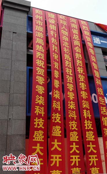 路边一栋楼上悬挂着二三十条红色条幅,全部是祝贺一家公司开业的。