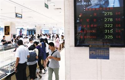7月22日,菜百金店、中国黄金旗舰店、王府井工美几大黄金卖场宣布下调金饰品价格,调整幅度为每克降7元。图为市民在菜百购买金饰。