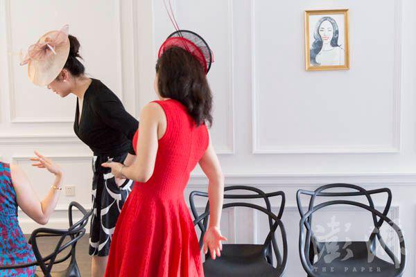 2015年7月10日,位于上海武康路的瑞雅礼仪学校,两名学员向何佩嵘请教佩戴礼帽时需要注意的事项。 本组图文均为澎湃新闻记者 周西野 图