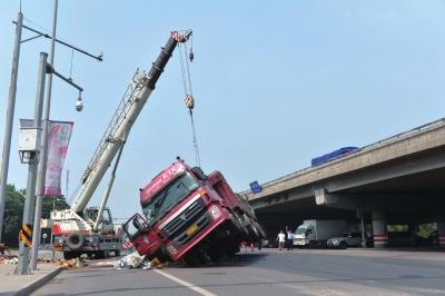 吊车将侧翻在路边的大货车吊起扶正。京华时报记者 赵思衡 摄