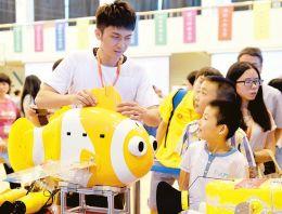 7月24日,一名参赛代表为小观众介绍水中机器人。当日,为期两天的2015国际水中机器人大赛在兰州交通大学拉开帷幕,包括中国、挪威、韩国等国家和地区的近60所院校的代表队前来参赛。