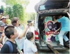七毛的花轿被搬下婚车,引来游客围观