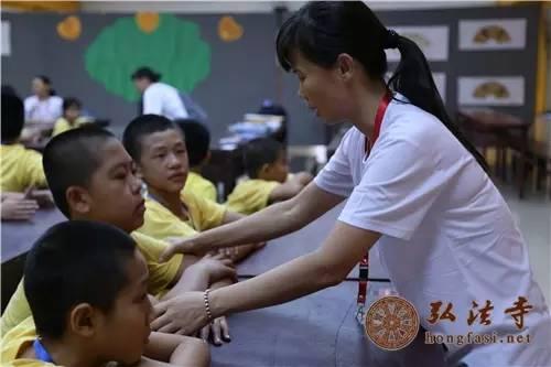 老师纠正学生坐姿,养成良好习惯 摄影:冯涛-印顺大和尚为弘法寺第