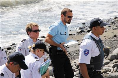 8月2日,法属留尼汪省首府圣但尼,警方人员在发现金属残片的海滩上搜寻调查。当地民众当天发现一块金属残片。新华社发