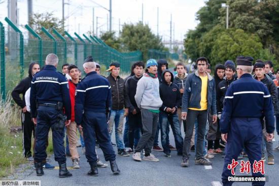 图为法国加莱警方阻拦偷渡者进入铁路。最近几天,超过4000名聚集在法国港口城市加莱的非法移民硬闯英吉利海峡海底隧道。 视频:法国:逾2000非法移民冲击英法海底隧道 来源:上海东方高清