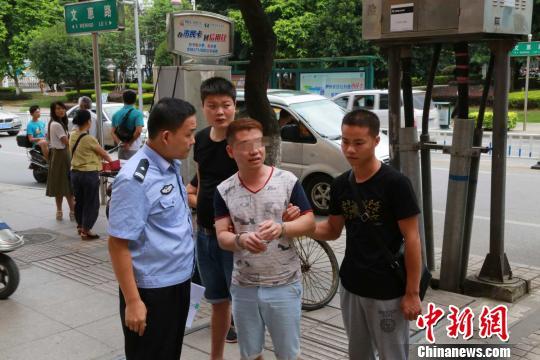 图为犯法怀疑人秦某明在承受警方询问。 韦崇结 摄