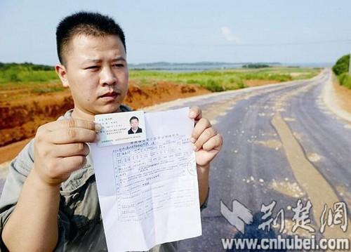 图为:张才方拿着父亲的身份证和殒命证实,站在未竣工的路途上