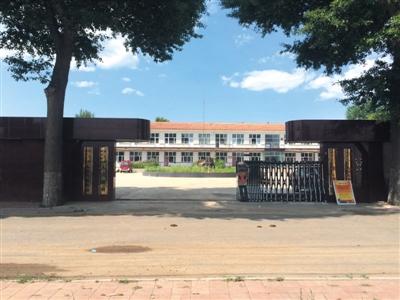 8月9日,文汇中学大门口已挂上乡当局四套班子的铭牌,红色修筑为文报告请示捐资重修的主教诲楼。新京报记者 林斐然 摄