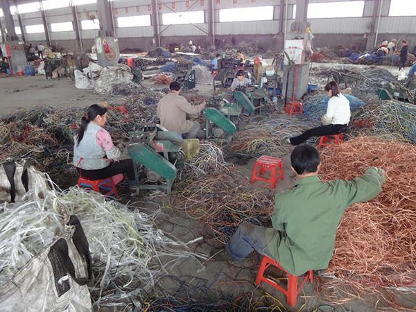 这是清远市最大的铜收受接管商清远金田公司的一个堆栈,工人们把电缆送进剥离器里。