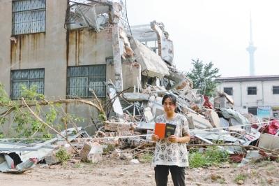 房�|朱密斯拿著屋宇�C件站在自家已被拆成�U墟的屋子前