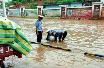 古蔺交警冒雨清掏排水口的场景,被网友点赞。
