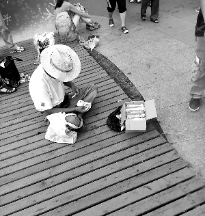 奥林匹克公园内一位游商坐在地上售卖冰棍。