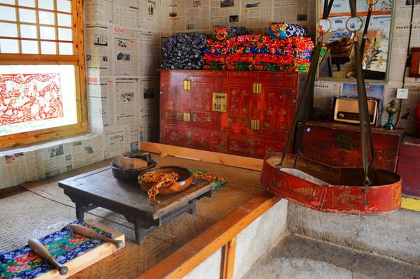 东北过去农村的房间都是这样的,一进屋有南北火炕,家具摆设家家如此