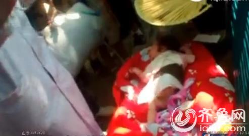 该弃婴的身边发觉了一个白色的塑料袋,内里装着一些孩儿用的被子和衣物,另有局部现金(视频截图)