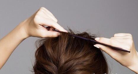 第三步:接着将头发梳成低马尾固定在脑后,并用发束缠绕固定.图片