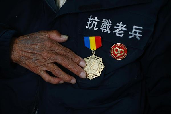 2015年3月3日,云南大理,一位老兵戴上多枚抗战留念章。CFP 材料