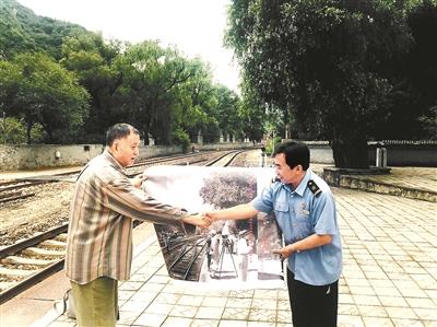 杨站长(右)接过孙明经儿子孙建三送来的青龙桥火车站老照片